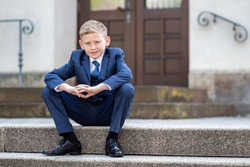 White blond 9 year old Boy in a Blue suit sitting on the stairs in Front of a church after his communion