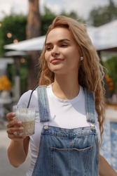 White blonde woman holding a glass of coffee latte in her hand. Portrait of a beautiful young adult girl. Summer terrace of an outdoor cafe