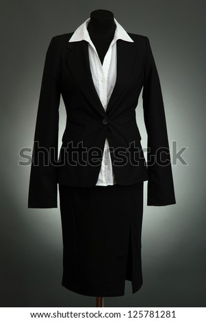 White blouse and black skirt with coat on mannequin on grey background