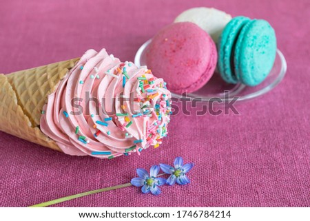 White, blue and purple macaroons, waffle cone with homemade marshmallow and spring flower on a linen napkin. Macarons or macaroons is French or Italian dessert. Close-up. Selective focus