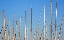 White boat and yacht masts with rigging on a blue sky background of Mallorca island. Spain