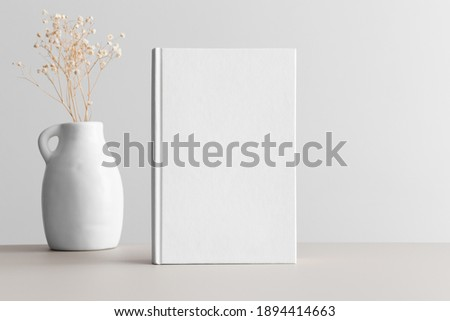 White book mockup with gypsophila in a vase on a beige table.