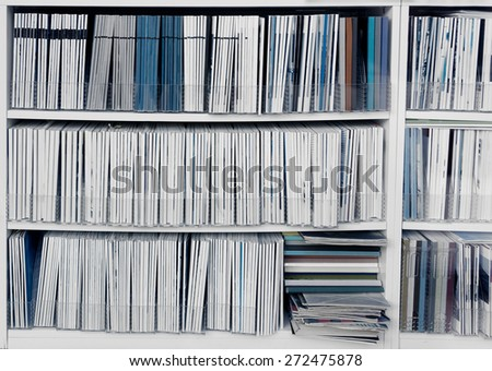 White bookcase with many reports, magazines or other publications