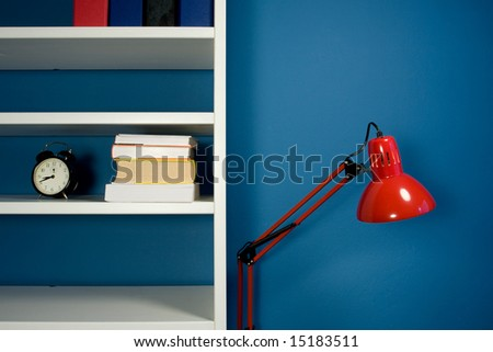 White bookcase with red reading lamp in blue room