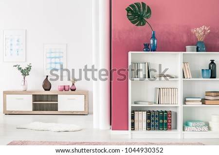 White bookcases and wooden shelf in spacious, white and red living room interior