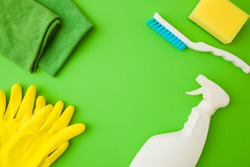 White bottle, rags, yellow sponge, gloves and brush. Cleaning set for different surfaces in kitchen, bathroom and other rooms. Green table background. Top down view. Closeup. Spring regular cleanup.