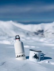 White bottle with animals printed on it and   an enamel mug with triangles printed in the mountain snow, Shar Mountains, Anteni