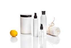 White bottles and one whole lemon isolated on white background. The concept for advertising cosmetics