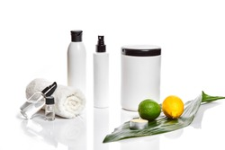 White bottles and whole lemon and lime isolated on white background. The concept for advertising cosmetics