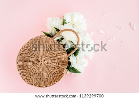 White bouquet of peonies in a straw bag on pink background. Minimal floral concept greeting card. Flat lay, top view.