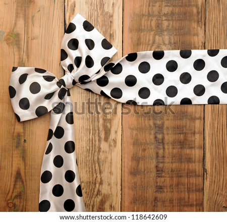 white bow with black dot on wooden background with copy space for your text