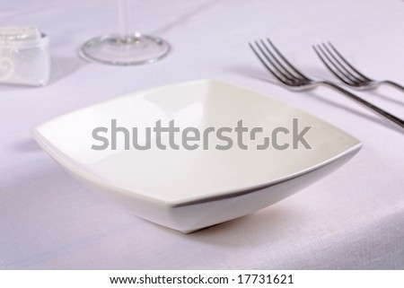 white bowl, forks and wine glass in a nice table setting.