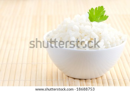 white bowl of boil chinese rice over bamboo