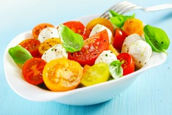 White bowl of fresh and healthy Mediterranean salad with mozzarella cheese, tomatoes and basil leaves and a fork over a blue table