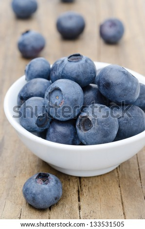 white bowl of fresh blueberries on a wooden background