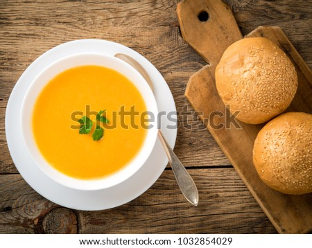 white bowl of pumpkin soup, garnished with parsley on wooden background, top view.