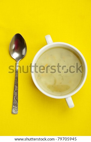 White bowl of soup on a yellow background next to a spoon is