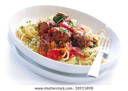 White bowl of spaghetti and meatballs in a bolognese sauce.  Isolated on white.