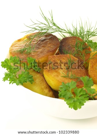 White bowl with baked potatoes and leaves of parsley
