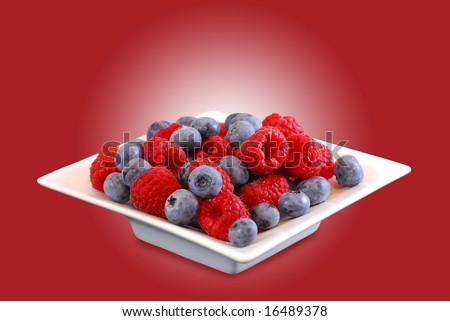 White bowl with raspberries and blueberries on a red background (easy to remove because clipping path)