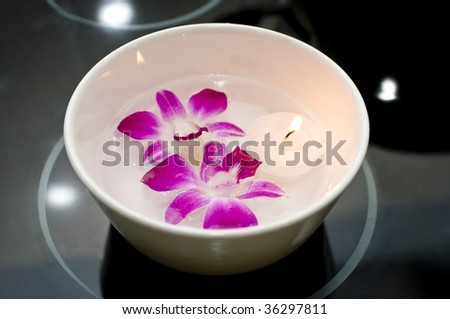 White Bowl with Water, Purple Orchids and Floating Tea light Candle on Black
