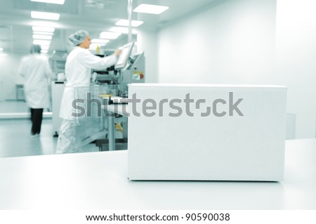 White box at automated production line at modern factory, people working in background