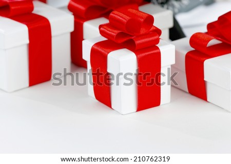 White boxes with gifts decorated with red ribbons on white background