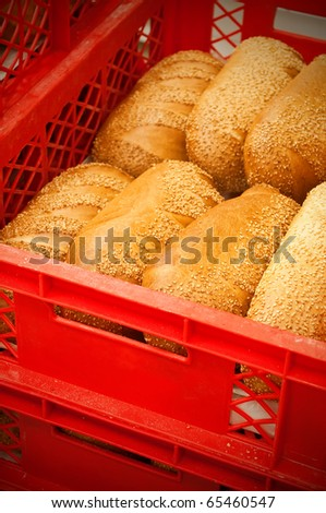 White bread loaves with sunflower seeds in a plastic crate.