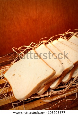 White breads on chopping board and straws with wooden background
