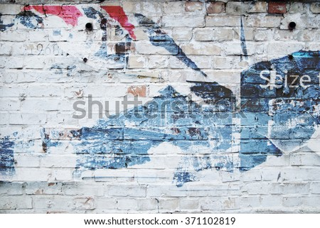 white brick wall and ripped street poster