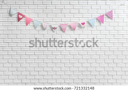 White brick wall decorated by colorful and pink cartoon flags for children or baby shower party event #721332148