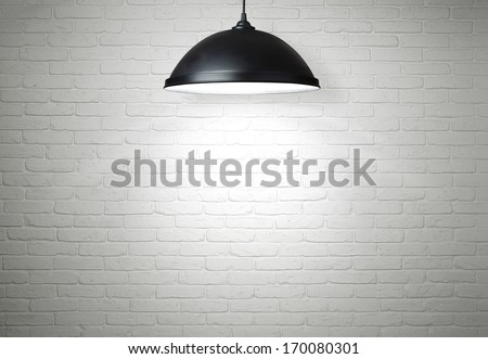 White brick wall illuminated by the ceiling lamp with copy space
