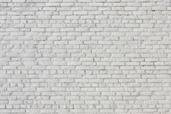 White brick wall. Outer wall of the urban building. Surface rough texture masonry. Bright cleaned brickwork.