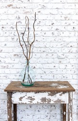 White brick wall with an unexpected pop of color from a repurposed green bottle accented with willow branches sitting on an antique distressed table.