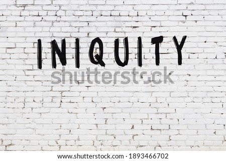 White brick wall with inscription iniquity handwritten with black paint Сток-фото ©