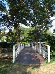 White bridge in the park across the ditch, greenish scenery, sunny day.