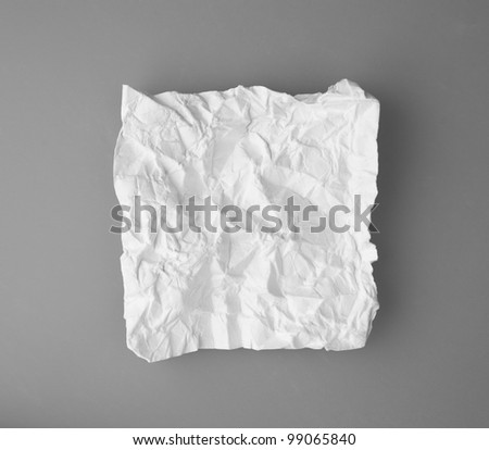 White broken and creased paper note isolated on a gray background. - stock photo