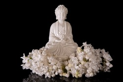 White Buddha framed by white lilac flowers on a black background with reflection