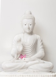 White Buddha in blessing pose with flower