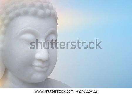 White Buddha portrait isolated on light blue background.