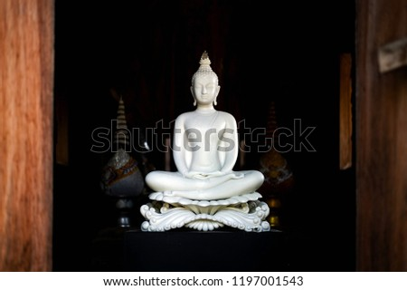 white buddha statue in thai lanna temple with soft-focus and over light in the background