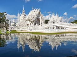 White buddhist temple reflected in the lagoon