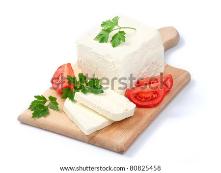 White Bulgarian cheese, arranged with tomatoes and parsley on cutting board