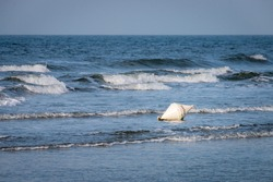 """White buoy with the german word """"surfen"""" (engl. surfing) in the water on a beach against sky."""