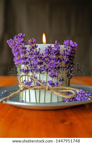 white  burning candle decorated with lavender on pewter plate #1447951748