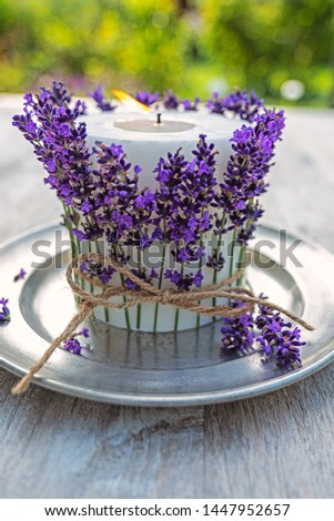 white  burning candle decorated with lavender on pewter plate  #1447952657