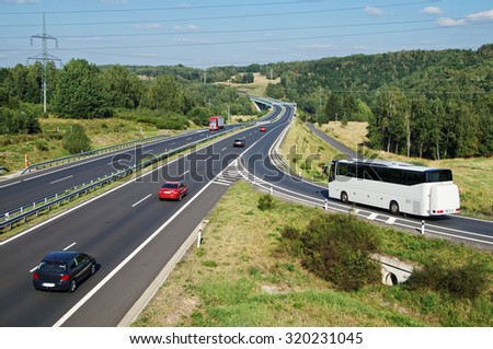 White Bus arriving to the asphalt highway on the slip road in a wooded landscape. Red passenger cars and truck driving on the highway. Electronic toll gate in the distance. View from above.