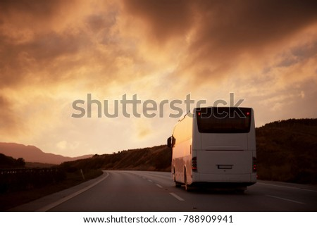 White bus driving on road with sunset view