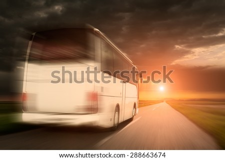 White bus in fast driving on an empty open road towards the setting sun in blurred motion.