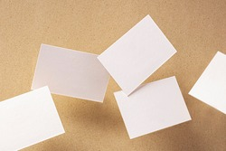 White business cards, floating on a brown paper background, a mock-up for design presentation